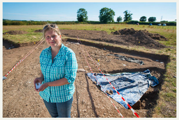 Danielle Wootton at Ipplepen excavation holding a newly found Roman brooch