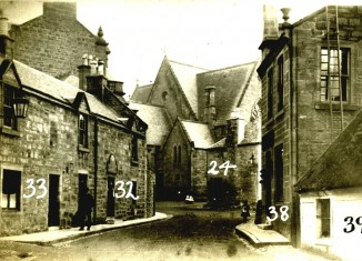 View looking up Lugar Street towards Old Cumnock Old Church in the early 1900s; the Tupp Inn is the building on the left (numbered 33 and 32)
