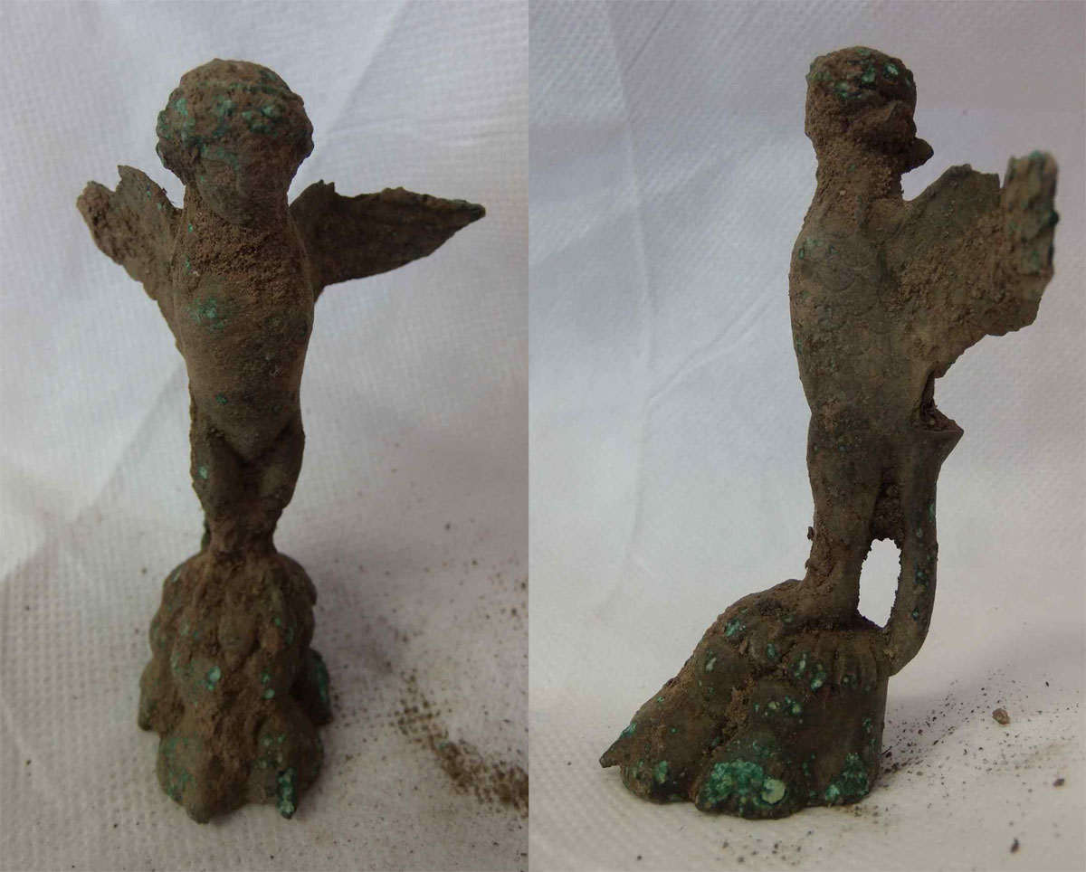 The image shows the figurine, before cleaning and conservation (from the front and in profile). Colchester Archaeology Trust