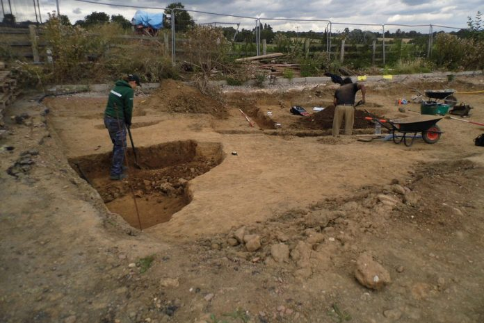 Archaeologists excavate some of the quarry pits. The Scheduled Monument lies behind the fence to the rear of the image. Image: ULAS
