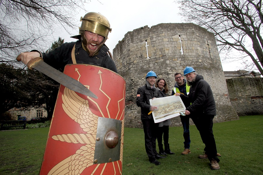 Gladiator Victorix from the Eboracum Roman Festival (left) urges (l-r) City of York Council's Archaeologist John Oxley and York Museums Trust Curator Emma Williams, Cllr Nigel Ayre and Mitchell Pollington of AOC Archaeology Group to find the lost amphitheatre through Ex Factum.