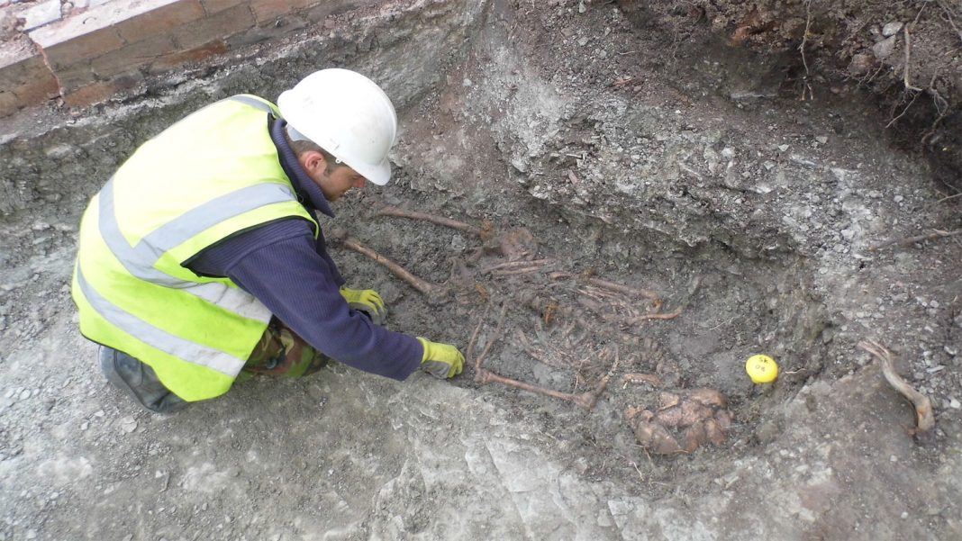 An archaeologist excavates one of the skeletons in the Roman cemetery at Western Road.